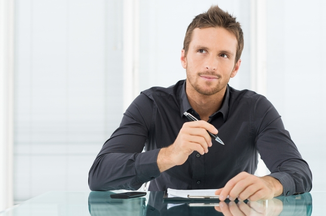 Young Businessman Thinking and Wondering While Writing a Paper Image Source: Writing and PR Studio (BigStock Images)