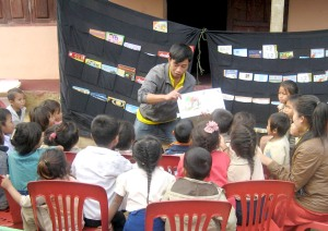 Addy Vannasy reads to village children on Discovery Day in Laos