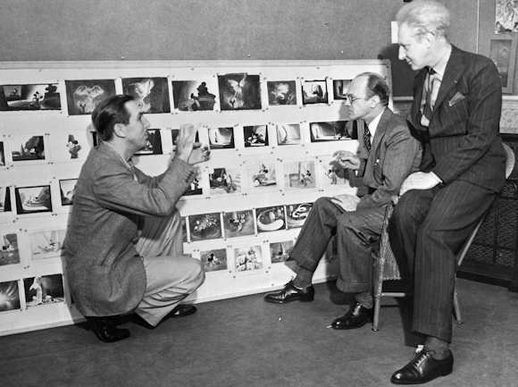 Walt Disney running through a storyboard with colleagues Image source: Kashinterest
