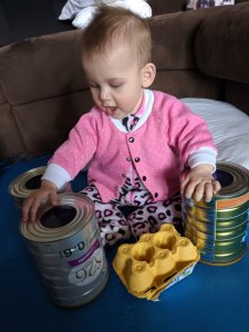 Baby Zoe with DIY drum kit made of empty formula tins