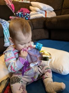 Baby Zoe playing with Tag rag made from reusable breast pad and ribbons